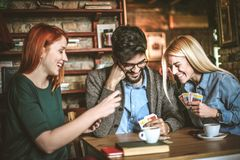 Young colleagues at cafe playing cards. royalty free stock images