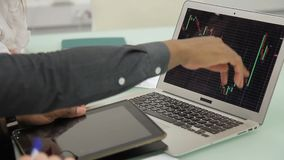 Young colleagues communicate, using laptop and tablet in modern office. Employees are at table with silvery device, look carefully and point to diagrams shown stock footage