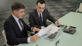 Young colleagues discussing documents sitting at table with laptop in company. Two men talk actively, examining papers and gesture with hands. Successful stock footage