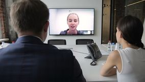 Young colleagues look at speaking coach on TV screen in company. Man and woman are sitting at table and looking attentively at female who is talking to their stock video footage