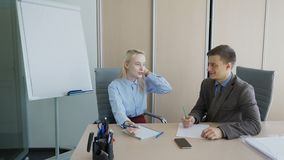 Young colleagues talk and write while sitting in leading company. Man and woman speak actively with friendly smiles, blonde makes notes on sheets with pen stock footage