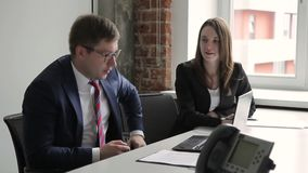 Young colleagues are talking while sitting in leading company. Man in glasses looks carefully at black laptop screen, speaking with smiling woman locating next stock video footage
