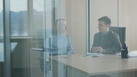 Young colleagues are talking while sitting in prosperous company. Man and woman speak actively, looking at each other and listening attentively. Prospective stock video footage