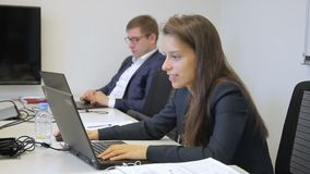 Young colleagues is working, sitting at table with laptops in company. Man in glasses and woman are engaged in operative affairs, looking at screens of black stock footage