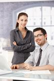 Young colleagues working smiling in bright office. Young colleagues working and smiling in bright office royalty free stock photos