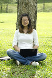 Young college asian girl using laptop outdoor Royalty Free Stock Photography
