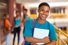 Young college boy holding books Royalty Free Stock Photo