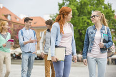 Young college friends walking on street Stock Photo