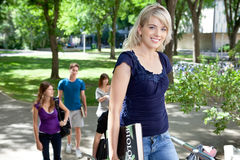 Young college girl. Pretty college girl going to college with friends in background Royalty Free Stock Image