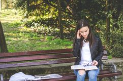 Young college or school girl feeling sick with strong headache pain or migraine attack while she sitting on the bench in the park. Reading books and study for royalty free stock photography