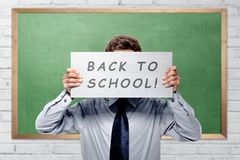 Young college student with back to school message. Against chalkboard background stock image