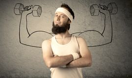 Slim male wants to be strong. A young college student with beard and glasses posing in front of grey background, thinking about lifting weight with big muscles Royalty Free Stock Images