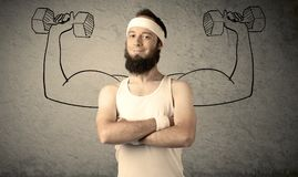 Slim male wants to be strong. A young college student with beard and glasses posing in front of grey background, thinking about lifting weight with big muscles Royalty Free Stock Photo
