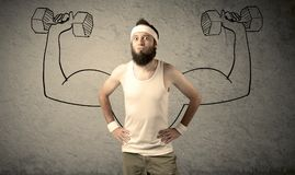 Slim male wants to be strong. A young college student with beard and glasses posing in front of grey background, thinking about lifting weight with big muscles Stock Image