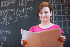 Young college student by the chalkboard/ Stock Photos