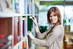 Young student selecting book in library Stock Photos