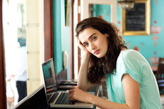 Young college student sitting at cafe with laptop Stock Images