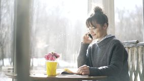 Young college student is studying in a cafe and picking up her phone stock footage