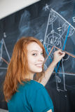 Young college student writing on the blackboard Stock Photo