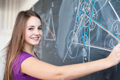 Young college student writing on the blackboard Stock Images
