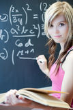 Young college student writing on the chalkboard Royalty Free Stock Photos