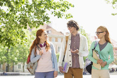 Young college students talking while walking on street Royalty Free Stock Photography