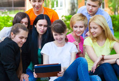 Young college students using tablet computer. While doing homework in the park Royalty Free Stock Photography