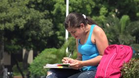 Female College Student Writing. A young Colombian adult female stock video footage
