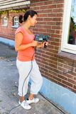Woman holding drilling machine on brick wall royalty free stock photography
