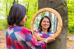 Woman looking at mirror in spring forest. Young Colombian woman looking at mirror in spring forest Royalty Free Stock Image
