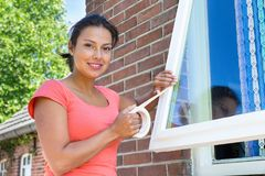 Woman sticking adhesive tape on glass of window Stock Images
