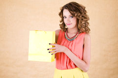 Young colorful dressed woman with color shopping bag Stock Photos