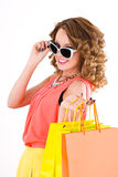Young colorful dressed woman with color shopping bags on white Stock Photos
