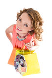 Young colorful dressed woman with color shopping bags on white Royalty Free Stock Photography