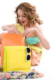 Young colorful dressed woman with color shopping bags on white Royalty Free Stock Photos