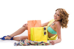 Young colorful dressed woman with color shopping bags on white Royalty Free Stock Image