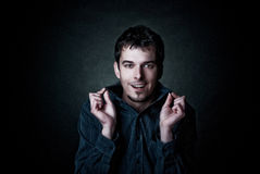 Young comic smiling man on a dark background. Young, smiling man holding fingers by ends of the collar. Photo like the comic Stock Photography