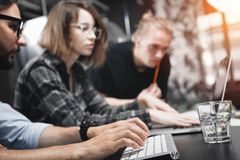 Young company of creative men and women working for modern devices in loft space. Coworking team is working on new idea and strata. Young company of creative men stock image