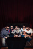 Young company in 3d glasses watch tv, top view. Young company of people in 3d glasses watch tv show at home. Five friends have fun entertainment sitting on couch Stock Photography