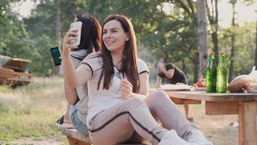 Young company of friends in the woods on the weekend. Girls take a selfie on the phone s camera, the guy makes a fire. stock video