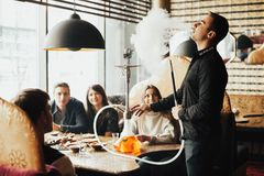 Young company is having fun and eating in bar. smoking a hookah, communicating in an oriental restaurant. The company plays board games royalty free stock image