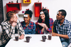 Young company play fun game together, home leisure. Young international company play funny game who I am. Four smiling people sit at the table with paper Royalty Free Stock Images