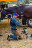 Murrurundi, NSW, Australia, February 24, 2018: Competitors in the King of the Ranges Horse Shoeing Competition. Young competitor adjusting the new horse shoe for stock image