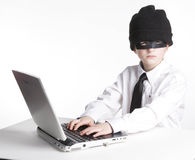 Young Computer Hacker. A Young male computer hacker types on his laptop computer Stock Photos