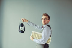 Young computer man holds keyboard and candlestick Royalty Free Stock Images