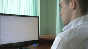 Young computer programmer coding at his desk stock video footage