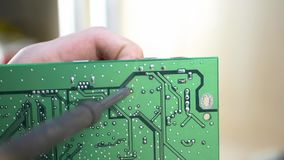 Young computer technician soldering green motherboard. In electronics workshop stock footage