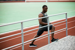 Young concentrated african male athlete stretching legs before the competition. At the stadium Stock Image