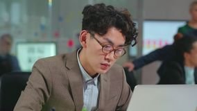 Young concentrated asian programmer in glasses stock video footage