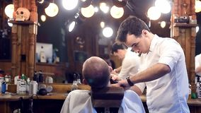 Concentrated guy barber cutting beard with clipper. Back view of male client. Hairdresser modern workplace on background. Young concentrated barber cutting beard stock video footage